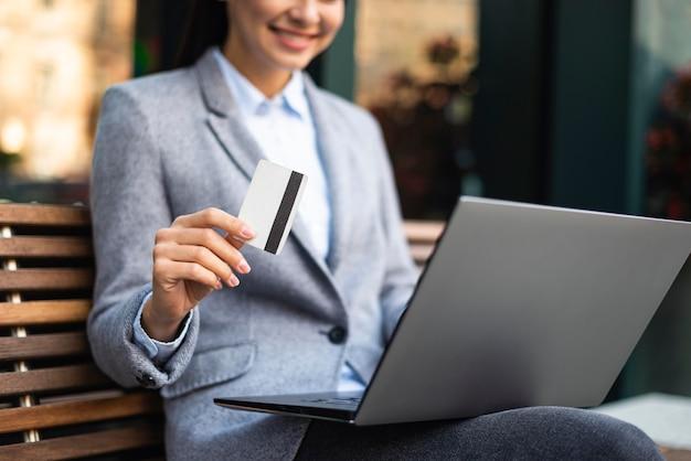 Sorridente empresária segurando um cartão de crédito enquanto usa o laptop