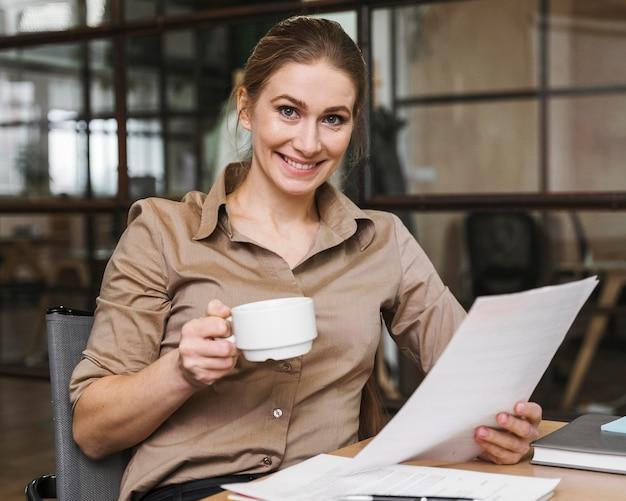 Sorridente empresária tomando café e lendo jornais
