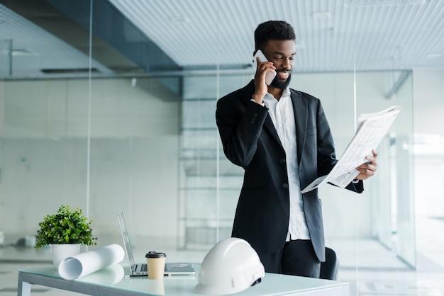 Sorridente empresário americano africano falando ao telefone com jornal e xícara de café no escritório
