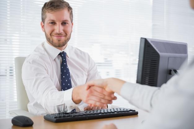Sorridente empresário apertando as mãos com um colaborador e olhando a câmera