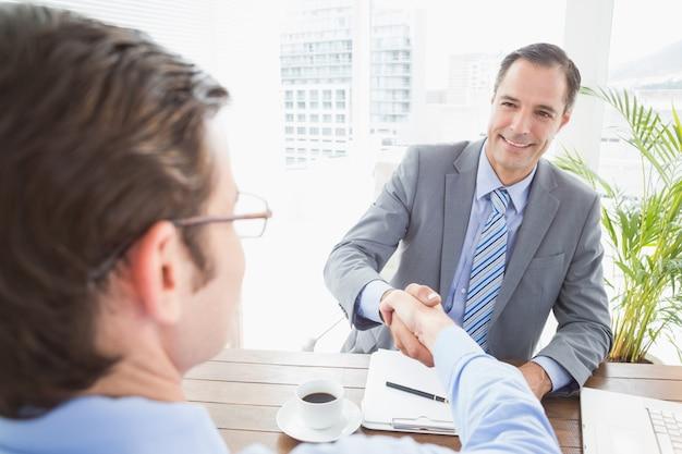 Sorridente empresário apertando as mãos com um colaborador