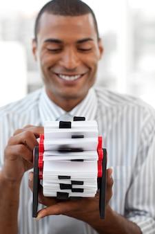 Sorridente empresário segurando um titular de cartão de visita