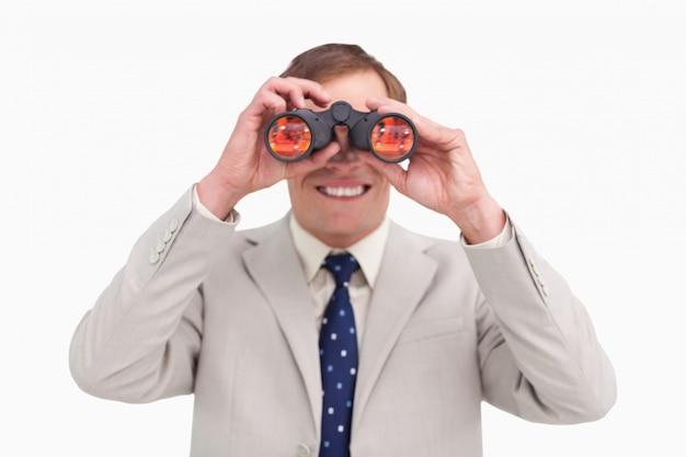 Sorridente empresário usando binóculos