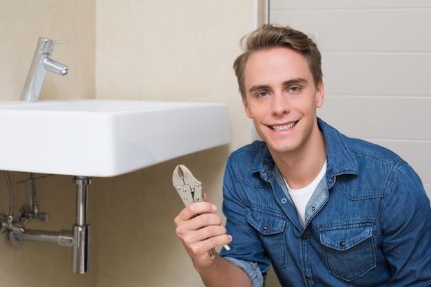 Sorridente encanador com chave pela pia no banheiro