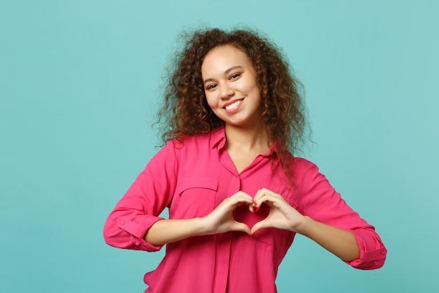 Sorridente encantadora garota africana em roupas rosa casuais, mostrando forma de coração com as mãos isoladas no fundo da parede azul turquesa no estúdio. conceito de estilo de vida de emoções sinceras de pessoas. simule o espaço da cópia.