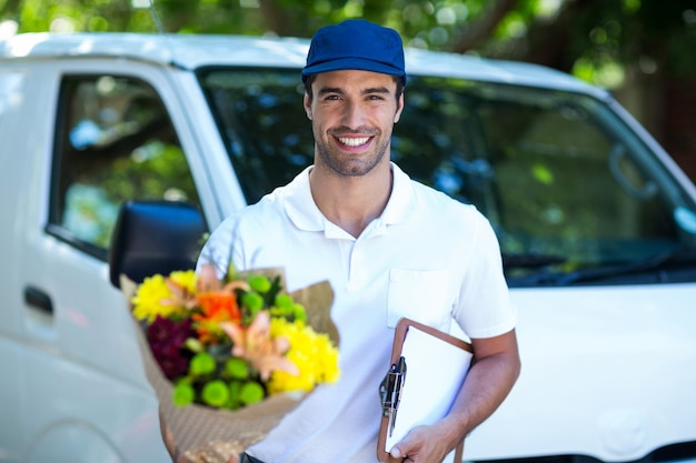 Sorridente entregador segurando a prancheta e buquê de flores