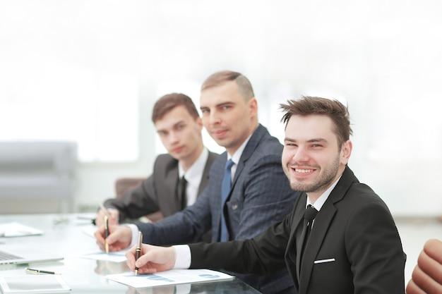 Sorridente equipe de negócios sentada na mesa no escritório.