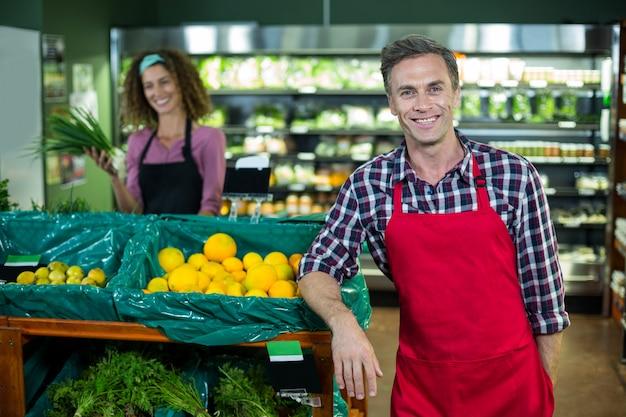 Sorridente equipe masculina em pé na seção orgânica