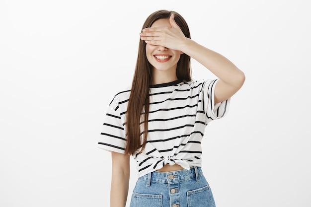 Sorridente esperançoso, garota atraente fecha os olhos com a mão e espera pela surpresa
