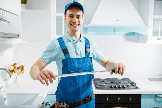 Sorridente fabricante de móveis masculinos de uniforme detém a fita métrica na cozinha. faz-tudo instalando guarnições, serviço de conserto em casa