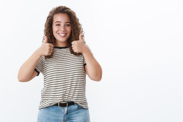 Sorridente, fofa, com sobrepeso, corpo positivo, menina feliz, olhos azuis de cabelos cacheados mostrando o polegar para cima, como um gesto de aprovação, sorrindo como uma roupa legal