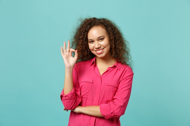 Sorridente garota afro-americana em roupas casuais, mostrando o gesto de ok, olhando a câmera isolada no fundo da parede azul turquesa no estúdio. emoções sinceras de pessoas, conceito de estilo de vida. simule o espaço da cópia.