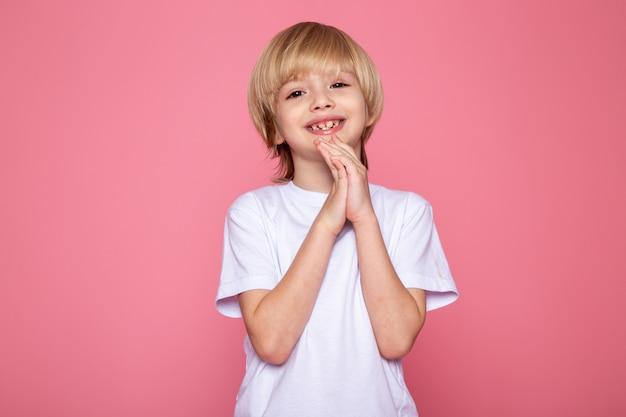Sorridente garoto loiro fofo doce adorável em camiseta branca na mesa-de-rosa