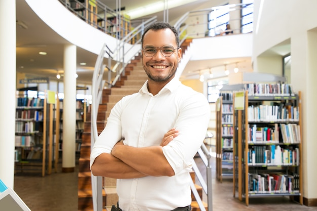 Sorridente homem afro-americano posando na biblioteca pública
