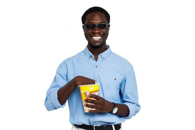 Sorridente homem bonito de óculos 3d detém um balde de pipoca em roupas casuais em branco