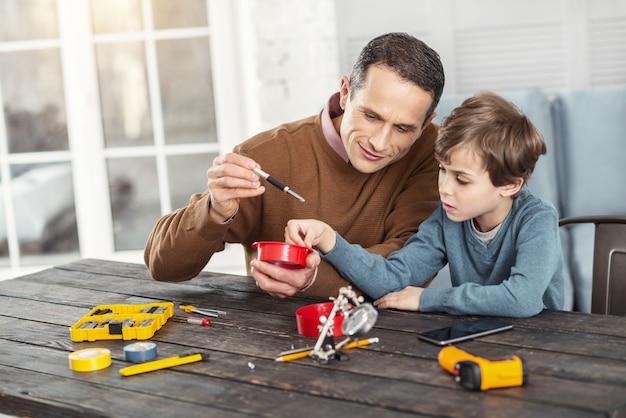 Sorridente. homem bonito e alegre de cabelos escuros mostrando instrumentos para seu filho enquanto está sentado na mesa e o ensinando