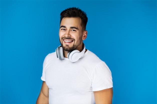 Sorridente homem bonito mantém seus fones de ouvido no pescoço