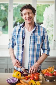 Sorridente homem cortar legumes em casa