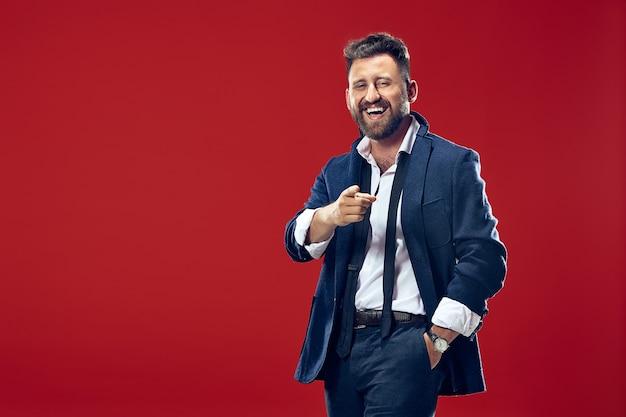 Sorridente homem de negócios apontar você, quero você, retrato de closeup de metade do comprimento no fundo vermelho do estúdio.