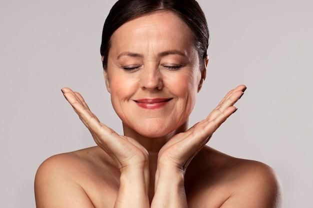 Sorridente idosa maquiada se preparando para cuidar da pele