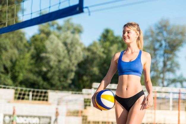 Sorridente jogadora de vôlei na praia segurando uma bola