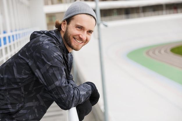 Sorridente jovem apto desportista a descansar após o treino no estádio, encostado a um carril