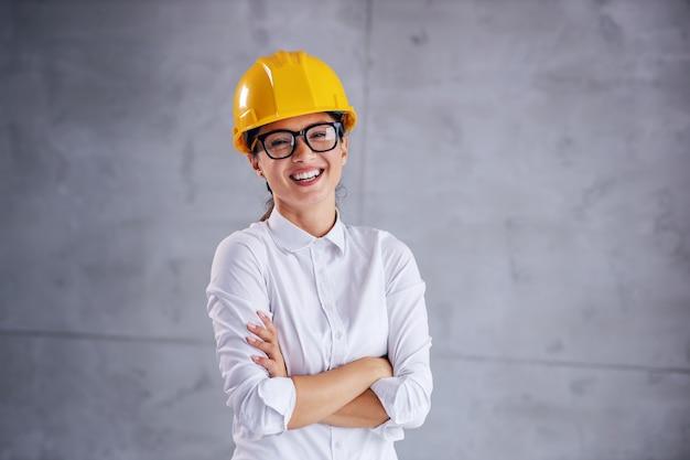 Sorridente jovem arquiteta com capacete na cabeça em pé com os braços cruzados.
