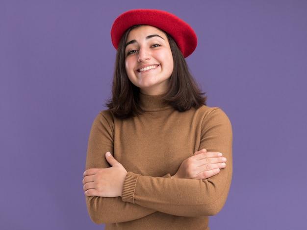 Sorridente, jovem, bonita, caucasiana, com chapéu boina em pé com os braços cruzados, isolada na parede roxa com espaço de cópia