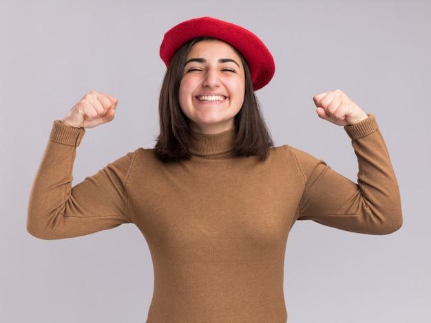 Sorridente, jovem, bonita, caucasiana, com chapéu boina, mantendo os punhos isolados na parede branca com espaço de cópia