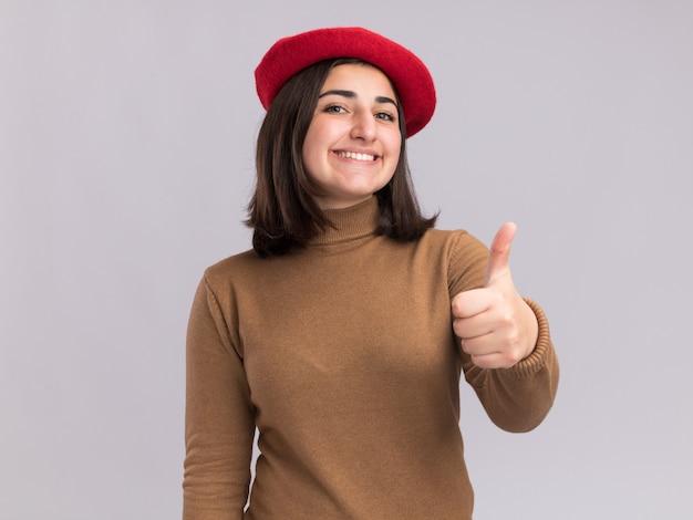 Sorridente, jovem, bonita, caucasiana, com chapéu boina, manuseando isolada na parede branca com espaço de cópia