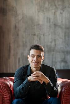 Sorridente jovem bonito sentado na poltrona contra parede cinza