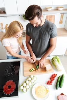 Sorridente jovem casal apaixonado em pé na cozinha e cozinhar