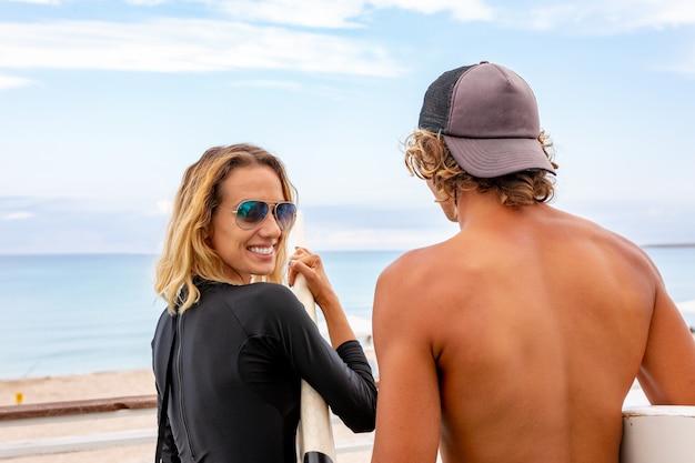 Sorridente jovem casal ativo surfistas relaxantes na praia depois do esporte