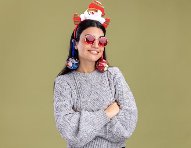 Sorridente jovem caucasiana com bandana de papai noel com óculos em pé com a postura fechada com enfeites de natal pendurados nas orelhas, isolada na parede verde oliva com espaço de cópia