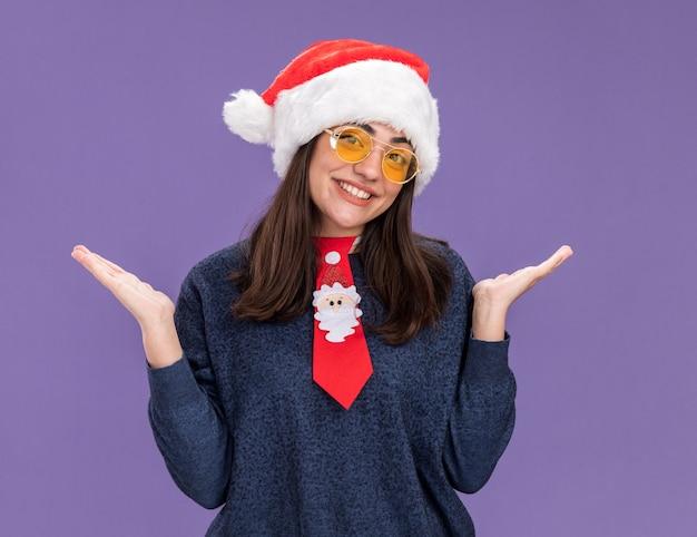 Sorridente jovem caucasiana de óculos de sol com chapéu de papai noel e gravata de papai noel de mãos abertas, isolado em um fundo roxo com espaço de cópia