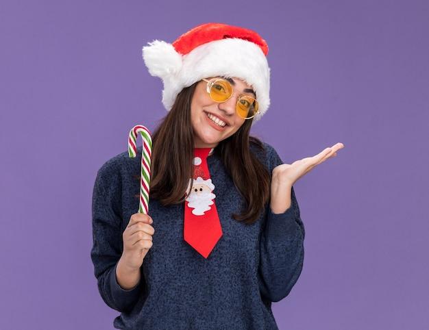 Sorridente jovem caucasiana de óculos de sol com chapéu de papai noel e gravata de papai noel segura o bastão de doces e mantém a mão aberta isolada no fundo roxo com espaço de cópia