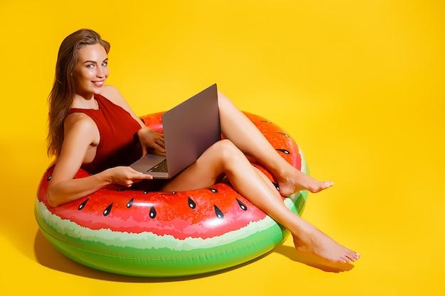 Sorridente jovem caucasiana em maiô isolado em fundo amarelo. conceito de resto de férias de verão de pessoas. sente-se no anel inflável de natação, trabalhe no computador laptop.