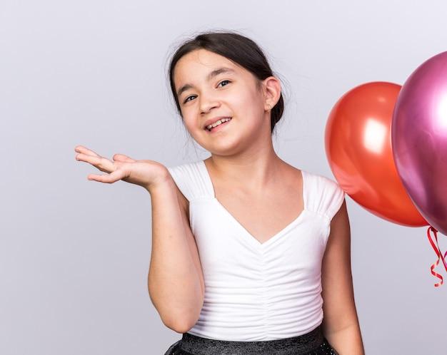 Sorridente jovem caucasiana em pé com balões de hélio, mantendo a mão aberta, isolada na parede branca com espaço de cópia