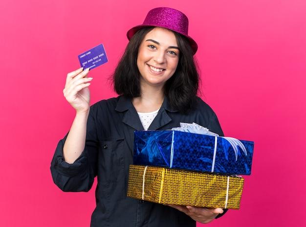 Sorridente jovem caucasiana festeira com chapéu de festa segurando pacotes de presentes e cartão de crédito isolados na parede rosa