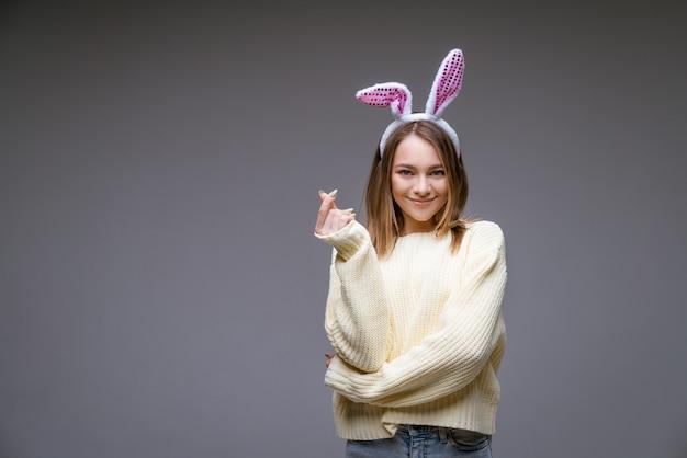 Sorridente jovem caucasiana, loira com orelhas de coelho, mostra um mini coração com dedos