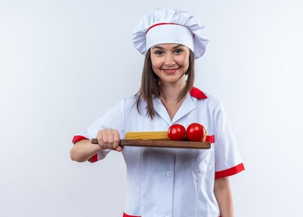 Sorridente jovem cozinheira vestindo uniforme de chef segurando espaguete com tomates numa tábua isolada na parede branca