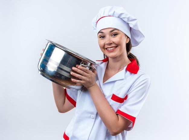 Sorridente jovem cozinheira vestindo uniforme de chef segurando uma panela isolada na parede branca
