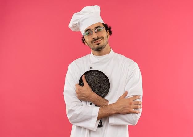 Sorridente jovem cozinheiro vestindo uniforme de chef e óculos, cruzando as mãos e segurando uma frigideira