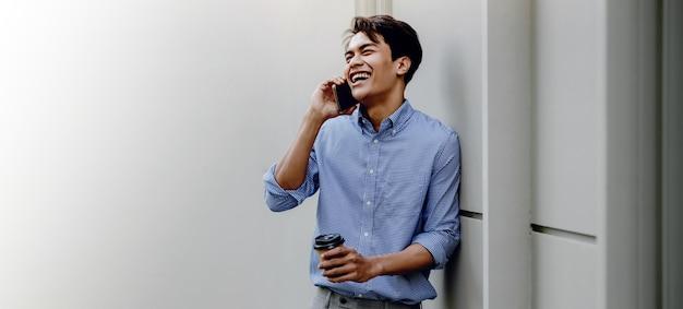 Sorridente jovem empresário asiático usando telefone celular na cidade. em pé com o café junto à parede. mais espaço de cópia com tamanho grande