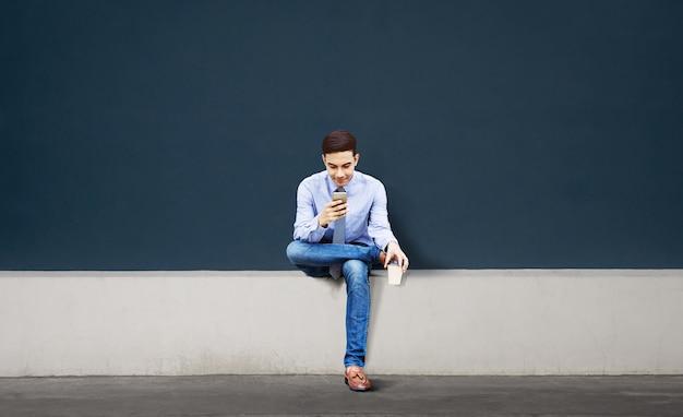 Sorridente jovem empresário asiático usando telefone celular na cidade. sentado contra a parede vazia
