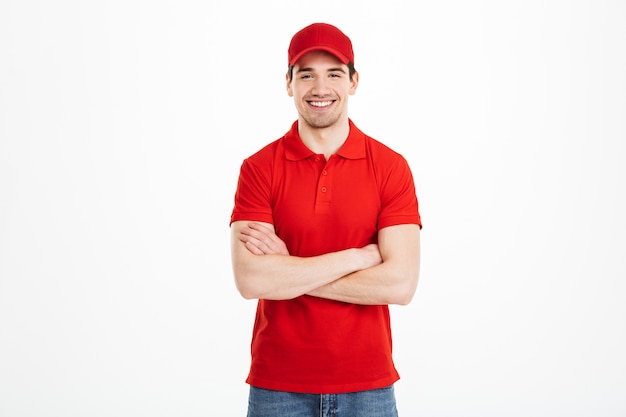 Sorridente jovem entregador de boné vermelho