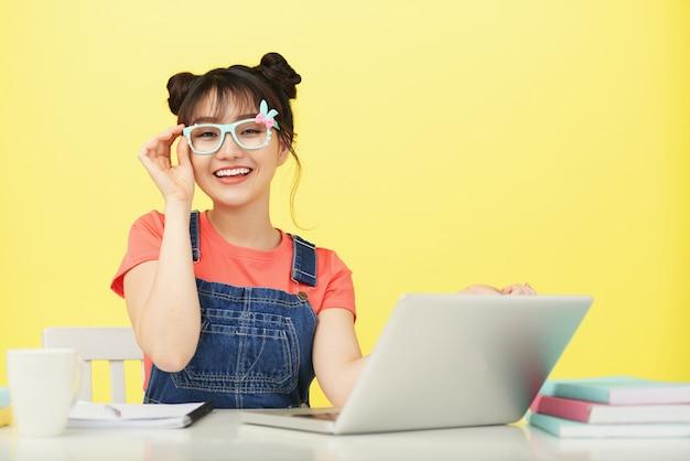 Sorridente jovem estudante asiática em óculos coloridos, sentado na mesa com o laptop