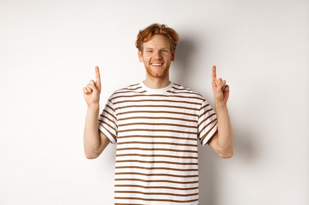 Sorridente jovem estudante do sexo masculino com cabelo ruivo mostrando o logotipo, apontando os dedos para cima e parecendo feliz, em pé sobre um fundo branco.