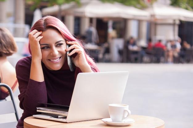 Sorridente jovem falando ao telefone e bebendo um café