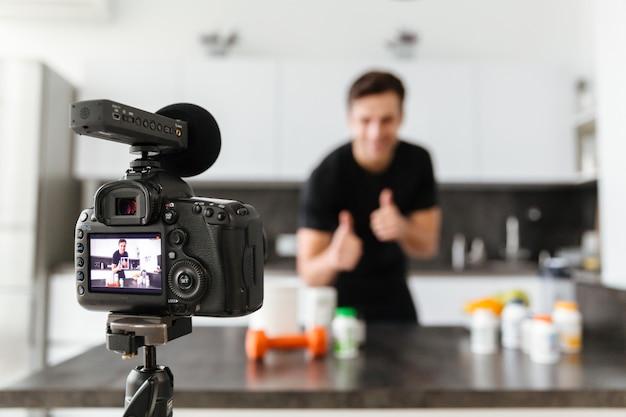 Sorridente jovem filmando seu episódio de blog de vídeo